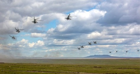 In this photo provided by Russian Defense Ministry Press Service on Tuesday, Sept. 11, 2018, Russian military helicopters fly, in the Chita region, Eastern Siberia, during the Vostok-201