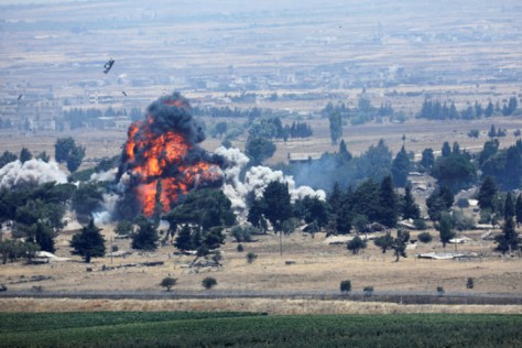 Ledakan terlihat di Quneitra, sisi Suriah pada perbatasan Suriah-Israel dilihat dari wilayah pendudukan Israel, Golan Heights, Israel, Minggu (22072018). (REUTERS)
