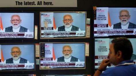 Seorang pria di Mumbai, India menonton pengumuman PM Modi soal keberhasilan India tembak jatuh satelit di luar angkasa (REUTERS)