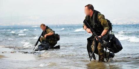 Dua anggota Special Boat Service muncul dari permukaan air dengan senjata siap tembak, 2010.[nam.ac.uk]