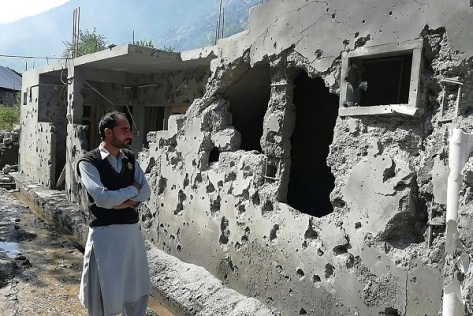 A man stands in front of his damaged house Sunday after cross-border shelling in Jora in the Neelum Valley of Pakistan-administered Kashmir. (Sajjad Qayyum - AFP Via Getty Images) E